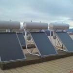 Grup de panouri solare cu boiler incorporat pentru producerea apei calde menajere montate pe un bloc de locuinte.